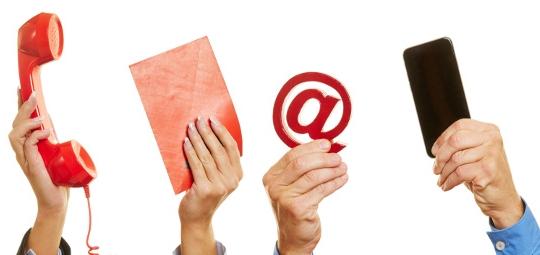 Hände halten viele verschiedene Mittel zur Kommunikation wie Telefon und Brief