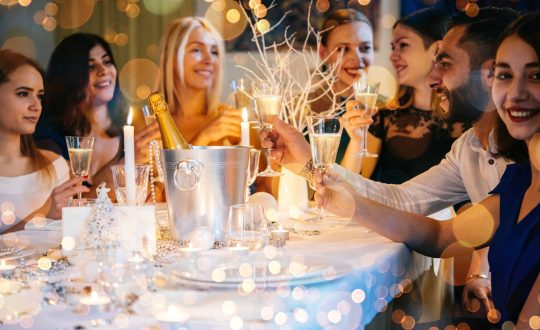 Friends celebrating Christmas or New Year eve. Party table with champagne.
