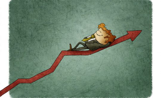 Relaxed smiling businessman lying on a graph going up. Concept of success