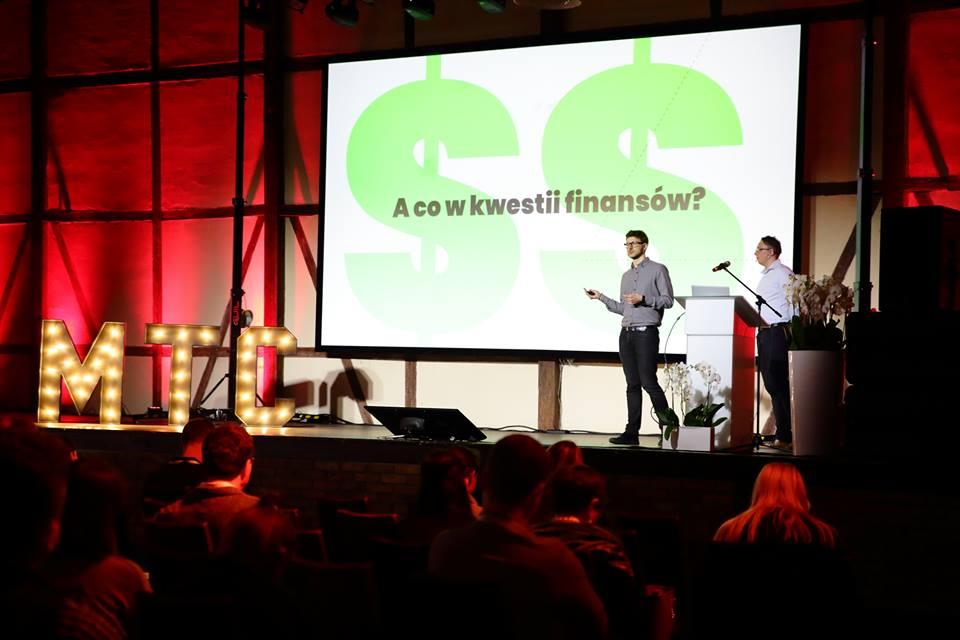 Konferencja o mobilnej bankowości: scena, dwóch prelegentów i prezentacja multimedialna