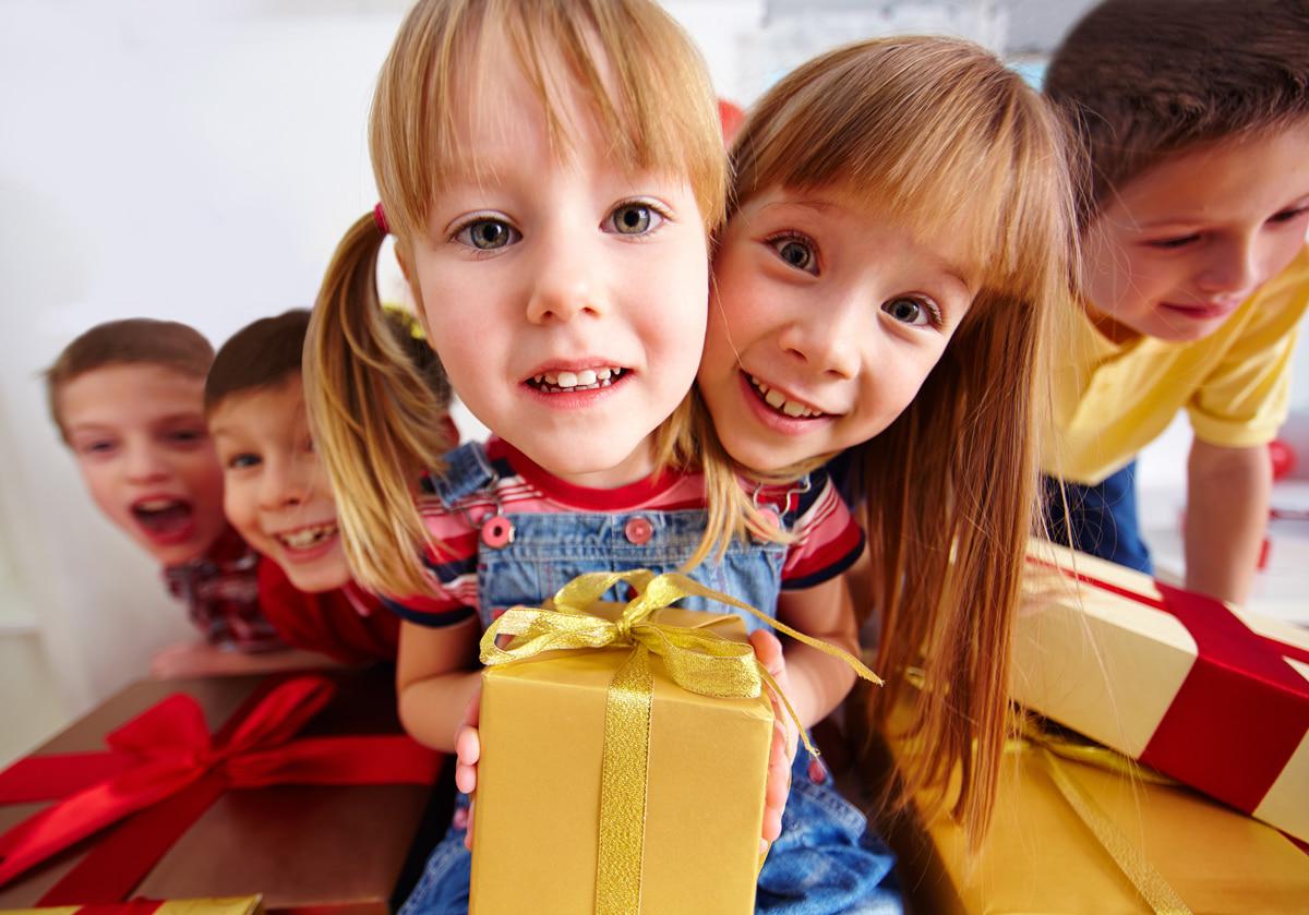 Uśmiechnięte dzieci z prezentem w dłoniach